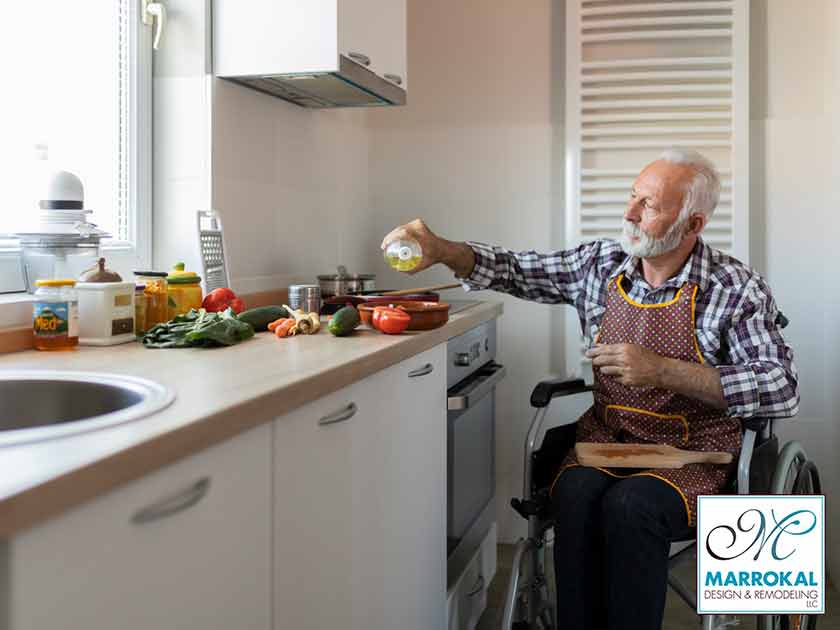 elderly man in wheelchair in kitchen cooking.