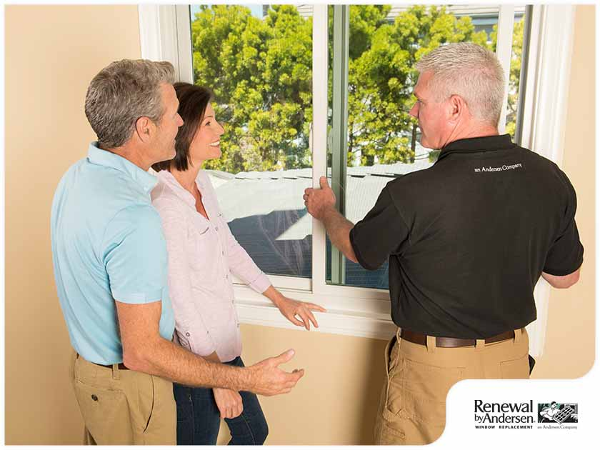 window installer discussing sliding windows with homeowners sliding patio doors