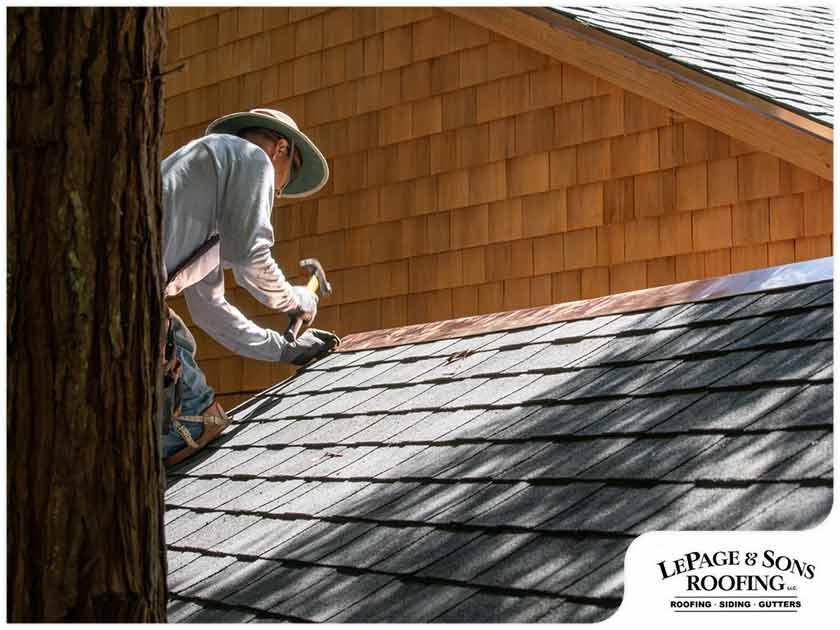 roofer hand nailing ridge shingles