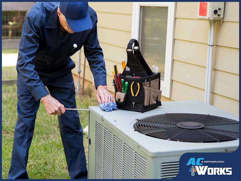 hvac technician checking outdoor unit