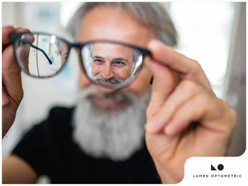 older man admiring his glasses