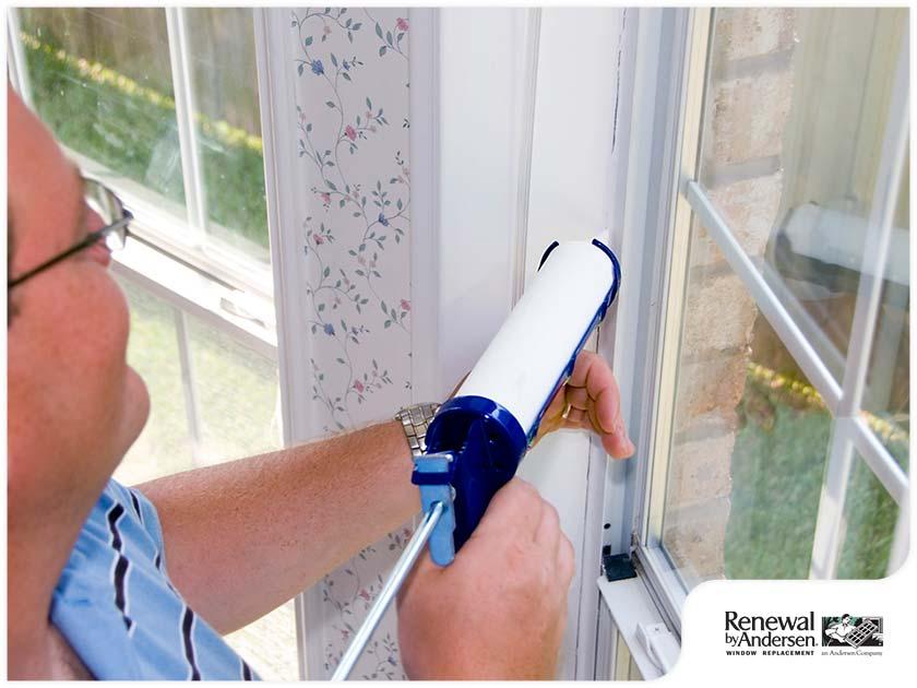 homeowner reapplying caulk window installation