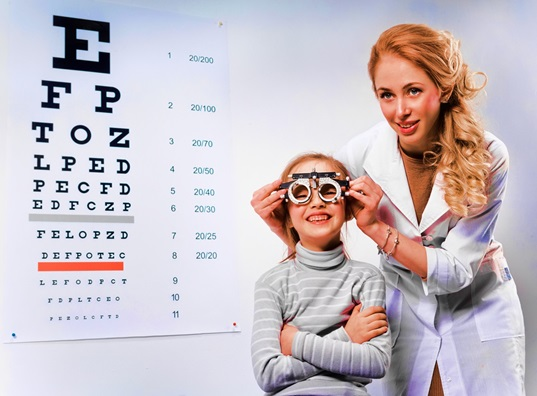 young girl undergoing eye test with phoropter